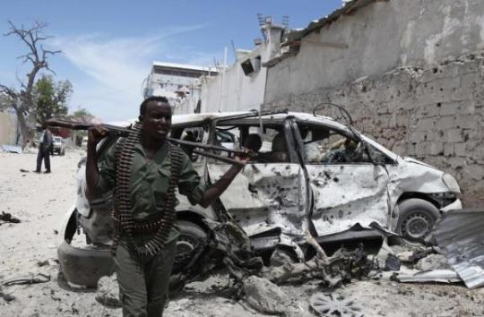 A Somali government soldier walks next to a car damaged in an explosion near Al Mukaram Hotel in Mogadishu March 15, 2014. (REUTERS/Omar Faruk)