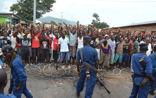 BUJUMBURA, BURUNDI - MAY 20: Burundian police officers rush to control the protesters during an anti-government demonstrations in Bujumbura, Burundi, on May 20, 2015. Regional leaders have called Burundi's President Pierre Nkurunziza, who had returned to the country after a failed coup, to postpone the country's parliamentary and presidential elections scheduled for 26 May and 26 June respectively. According to the United Nations' refugee agency, more than 105,000 Burndians have fled the country to seek refuge in neighboring countries such as Rwanda, DR Congo, and Tanzania. (Photo by Ndabashinze Renovat/Anadolu Agency/Getty Images)